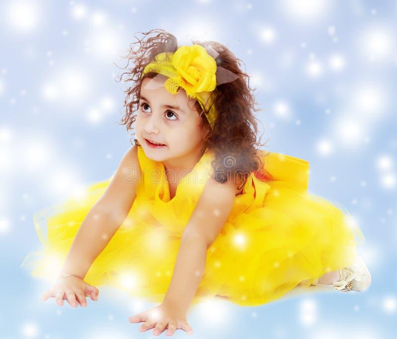 Маленькая девочка в желтом платье сидя на поле стоковое фото rf