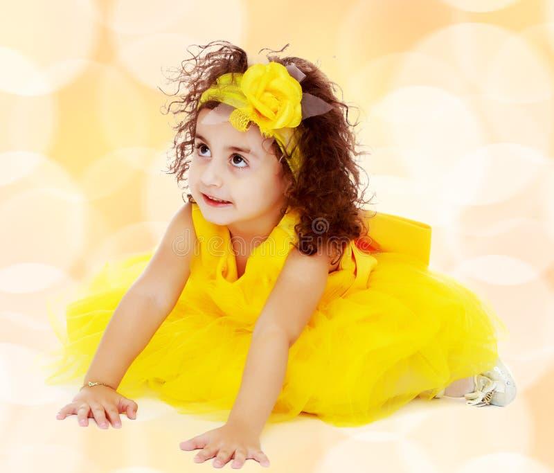 Маленькая девочка в желтом платье сидя на поле стоковая фотография