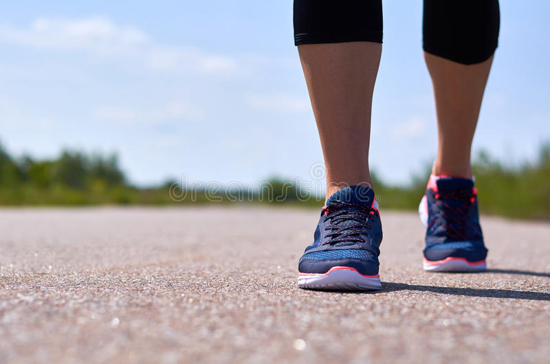 Маленькая девочка в идущих ботинках бежит вдоль дороги, только ее ноги видимы стоковые изображения