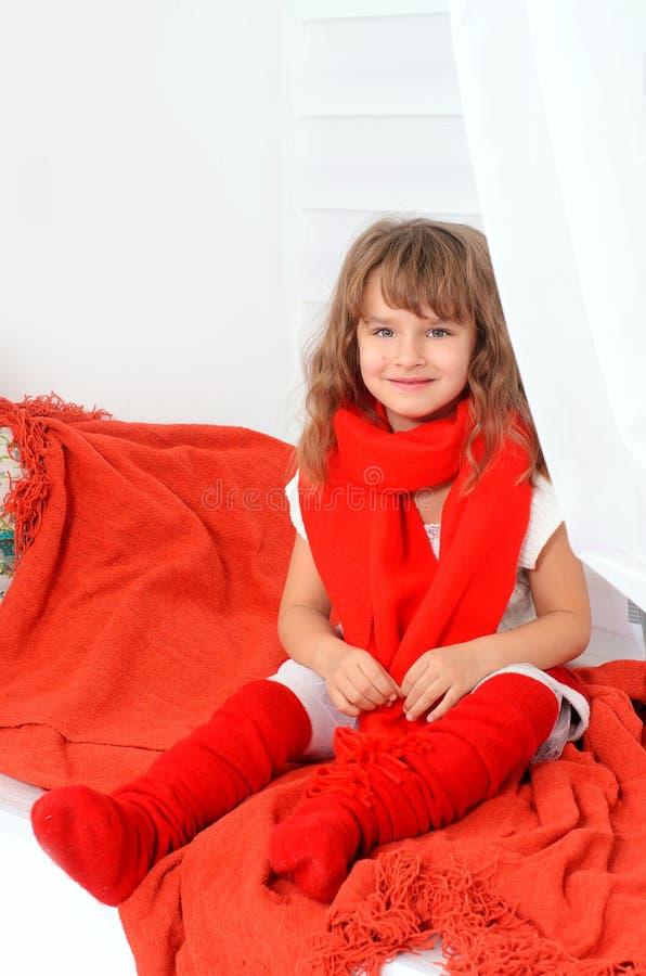 Маленькая девочка в красной и белом внутри помещения стоковое фото rf