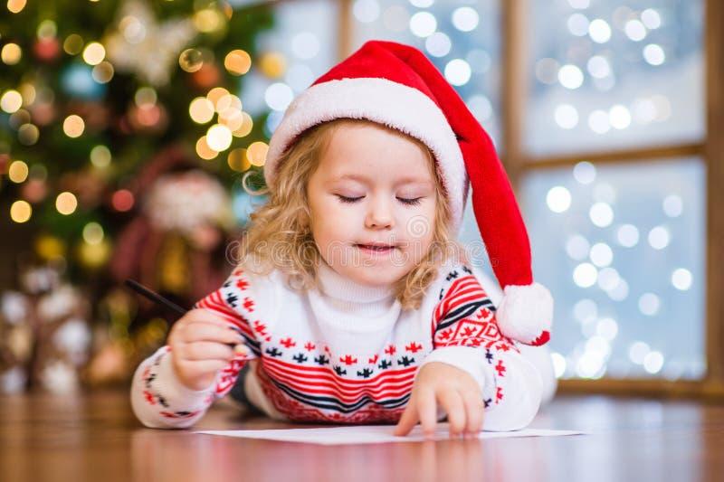Маленькая девочка в красной шляпе рождества пишет письмо к Санта Клаусу стоковое изображение rf