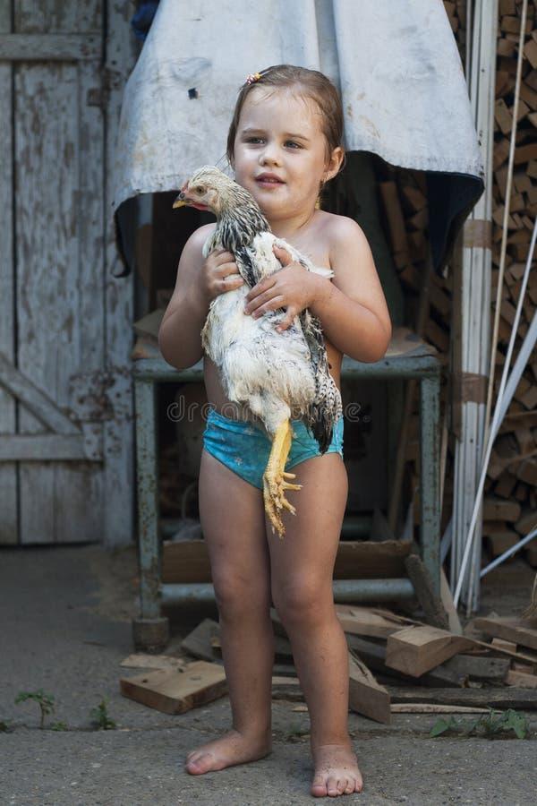 Маленькая девочка в купальнике держа цыпленка в ее оружиях стоковые фотографии rf