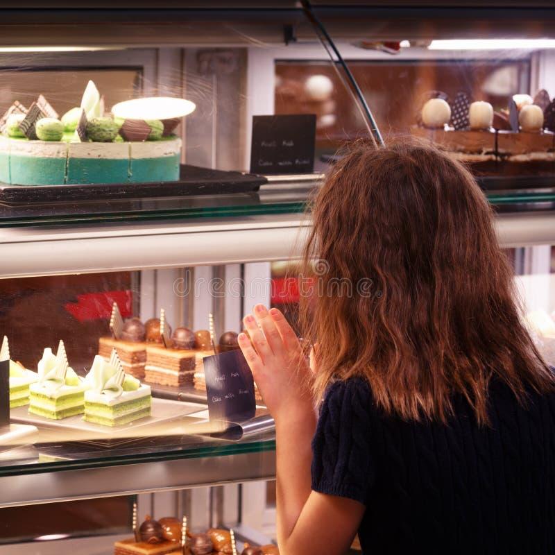 Маленькая девочка в магазине кондитерскаи смотря дисплей сладостно стоковое фото rf