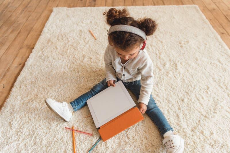 Маленькая девочка в наушниках сидя на поле и используя цифровую таблетку стоковая фотография rf