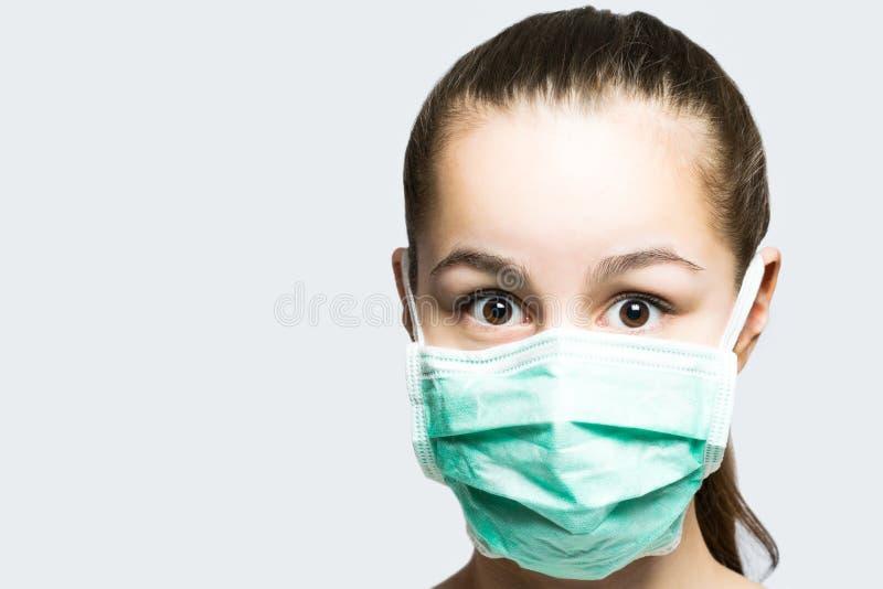 Маленькая девочка в докторах маскирует смотреть удивлена и сотрясена стоковое фото rf