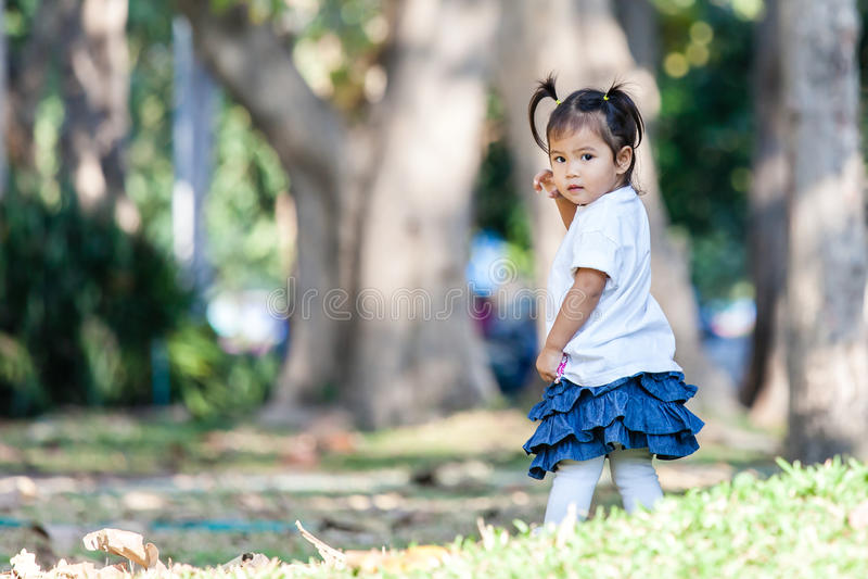 Маленькая девочка в парке и смотреть камеру стоковое изображение
