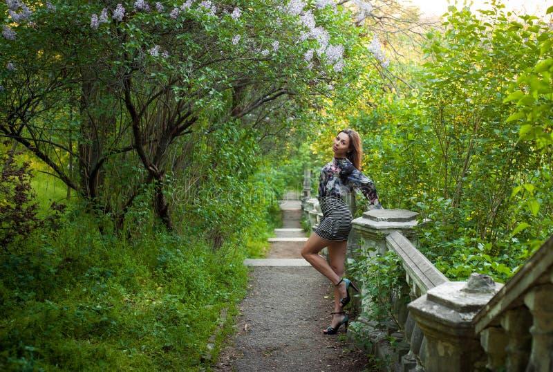 Маленькая девочка в полных безмятежности и умиротворении в красивом и элегантном платье на природе весной в парке стоковое фото