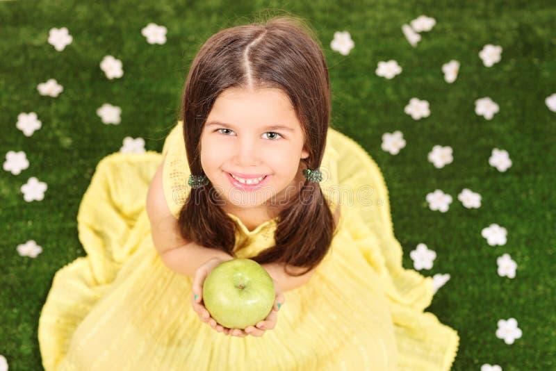 Маленькая девочка в причудливом желтом платье держа яблоко в луге f стоковые фотографии rf