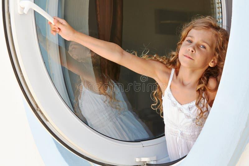 Маленькая девочка в платье раскрывает окно стоковое изображение rf