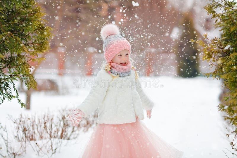Маленькая девочка в розовой юбке в зиме усмехается в парке и thr стоковое изображение rf