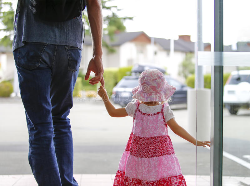Маленькая девочка в розовом платье держа father& x27; рука s стоковые фото