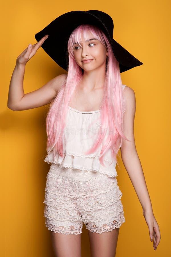 Маленькая девочка в розовых волосах представляя на желтой предпосылке стоковая фотография rf