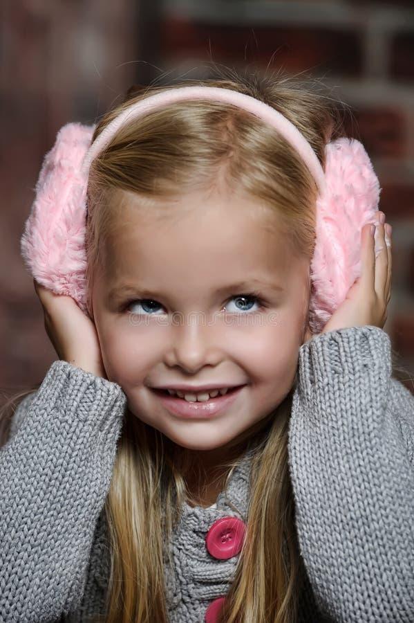 Маленькая девочка в розовых наушниках стоковые фотографии rf