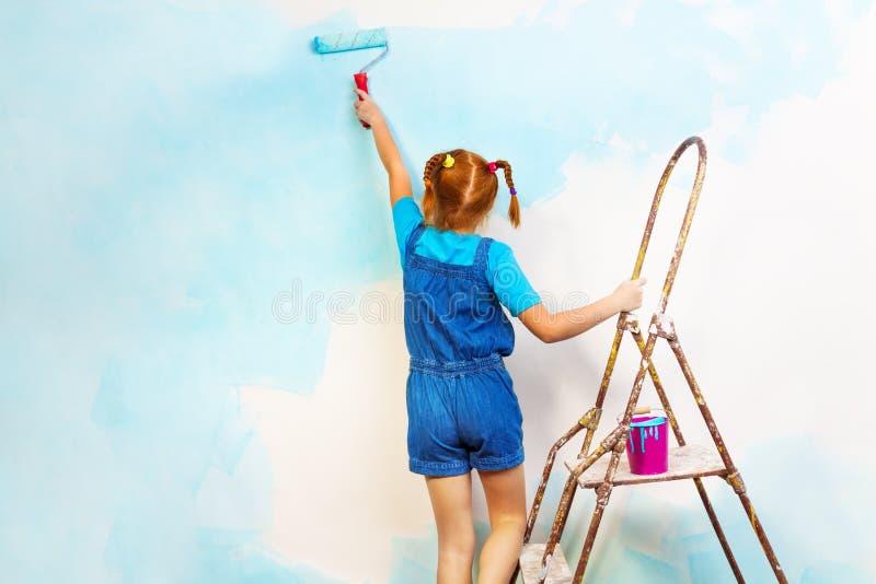 Маленькая девочка в сини красит стену на лестнице стоковое фото