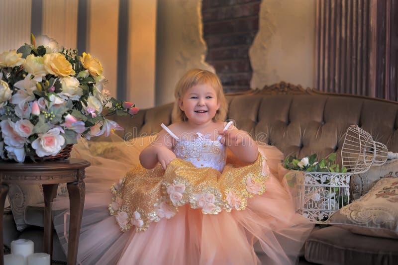 Маленькая девочка в сочном желтом цвете с белым платьем стоковое фото rf