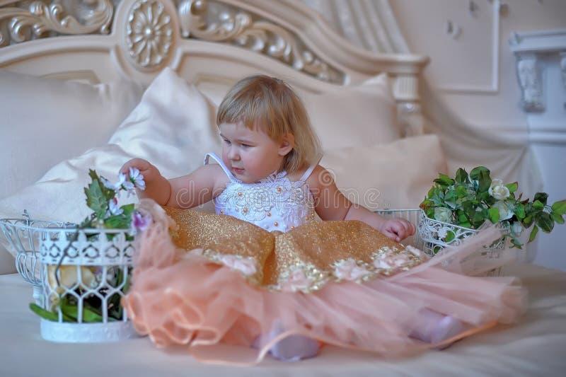 Маленькая девочка в сочном желтом цвете с белым платьем стоковые изображения rf