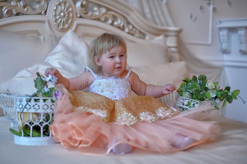 Маленькая девочка в сочном желтом цвете с белым платьем стоковая фотография rf