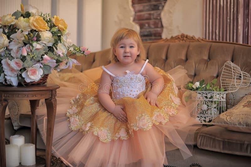 Маленькая девочка в сочном желтом цвете с белым платьем стоковые фотографии rf