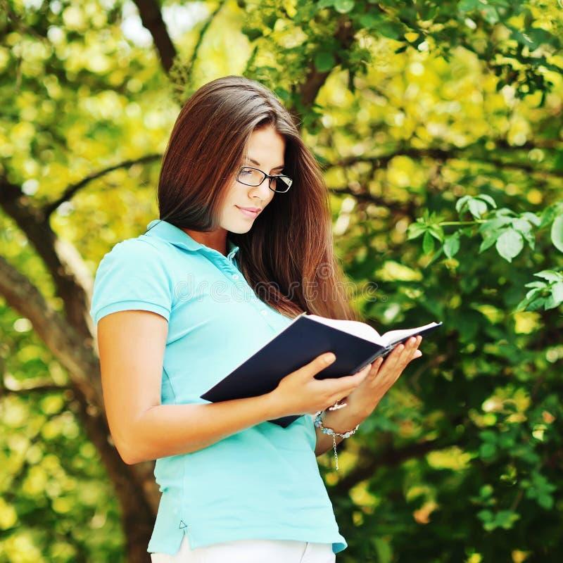 Маленькая девочка в стеклах читая книгу в парке стоковое фото
