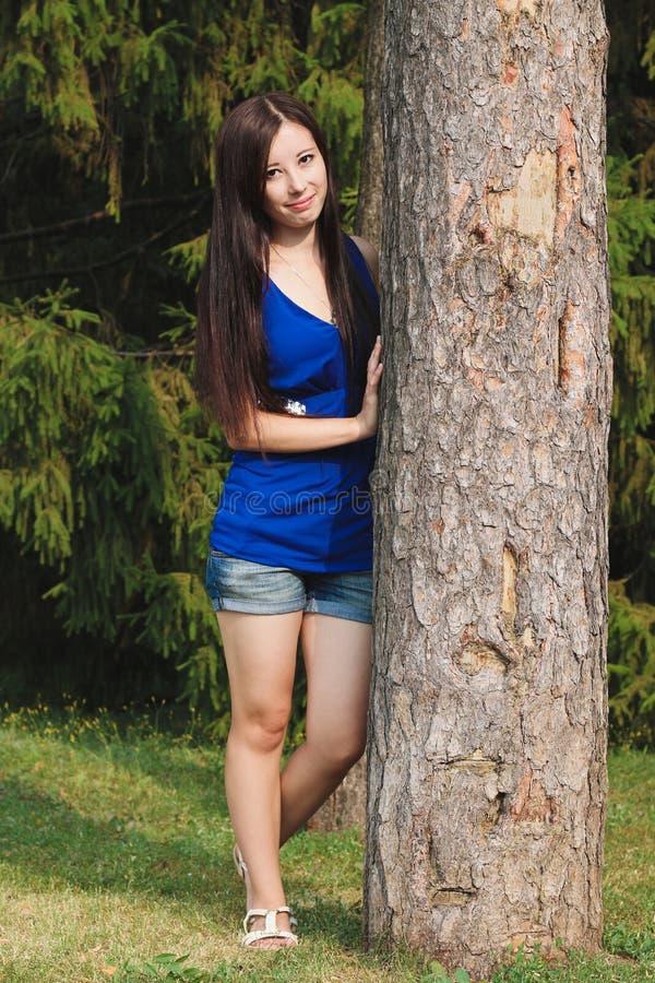 Маленькая девочка в шортах положилась против дерева в парке стоковое изображение