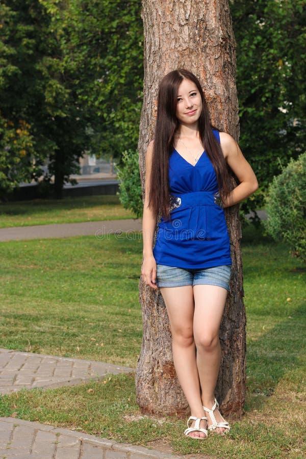 Маленькая девочка в шортах положилась против дерева в парке стоковые фотографии rf