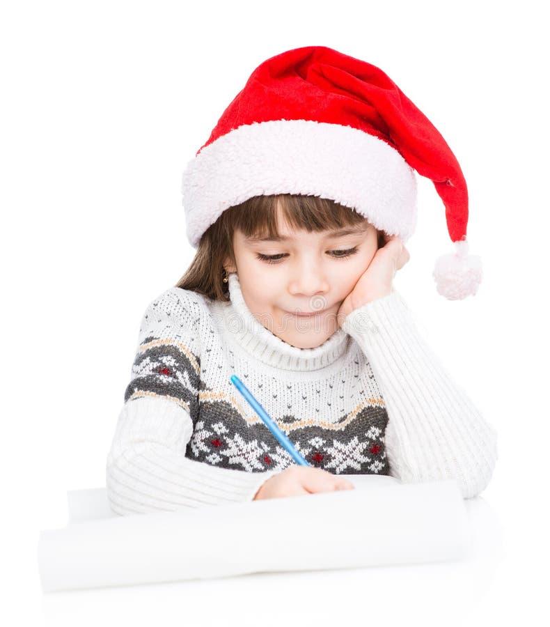 Маленькая девочка в шляпе Санты пишет письмо к Санте Изолировано на белизне стоковое фото rf