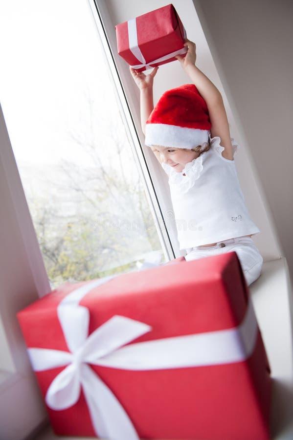 Маленькая девочка в шляпе Санты подняла подарок над ее головой сидя окном стоковое изображение rf