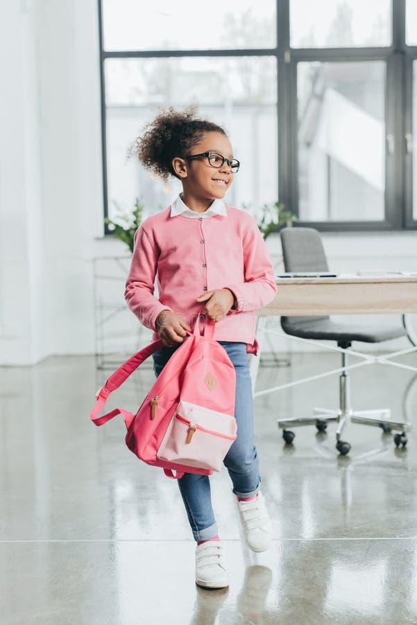 Маленькая девочка в eyeglasses держа розовый рюкзак пока стоящ внутри помещения стоковое фото