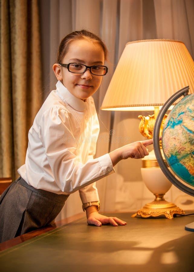 Маленькая девочка в eyeglasses указывая на глобус стоковая фотография