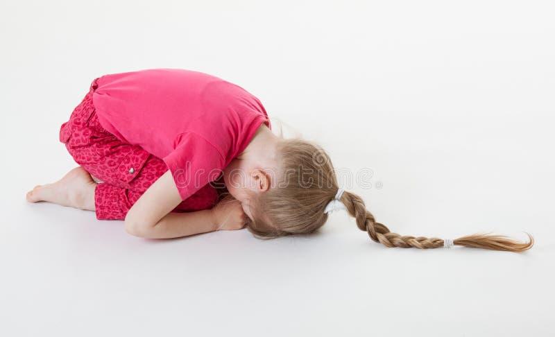 Маленькая девочка гнуть и закрывая ее глаза в positi сидеть на корточках стоковое изображение