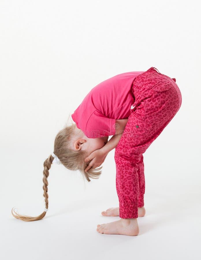 Маленькая девочка гнуть и закрывая ее глаза стоковые фотографии rf