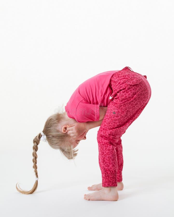 Маленькая девочка гнуть и закрывая ее уши стоковое изображение rf