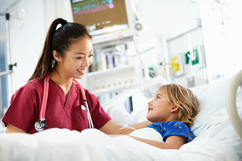 Маленькая девочка говоря к женской медсестре в отделении интенсивной терапии стоковые изображения