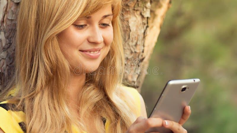 Маленькая девочка говоря на природе с smartphone стоковое изображение rf