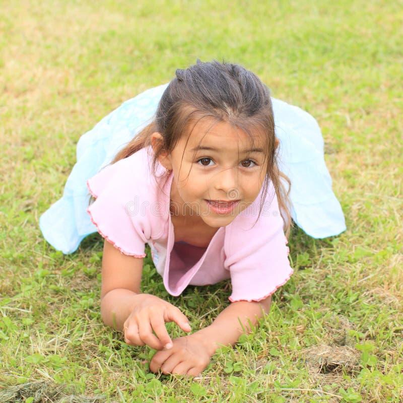 Маленькая девочка лежа на траве стоковое изображение rf