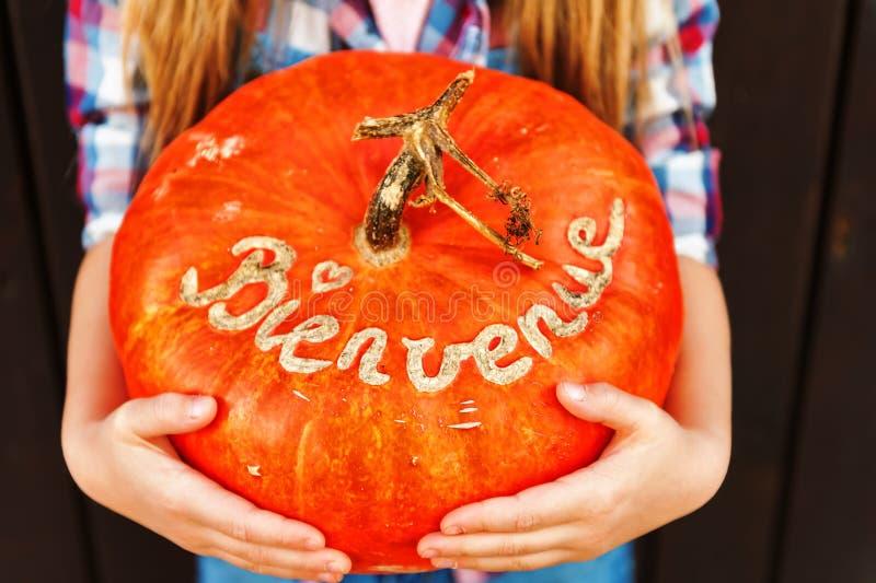 Маленькая девочка держа большую тыкву с французским знаком Bienvenue стоковое изображение