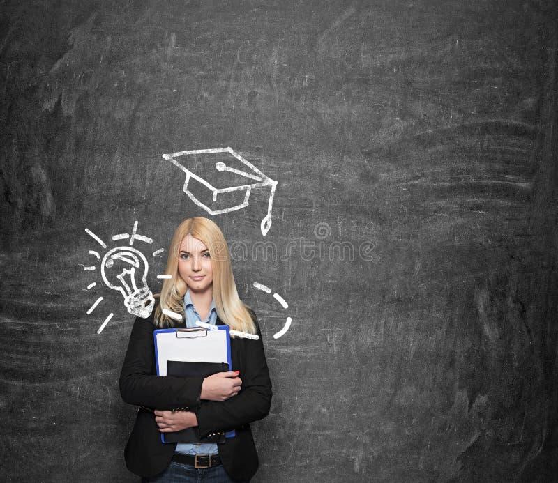 Маленькая девочка держа блокноты, нарисованную академичную шляпу над ей стоковое фото rf
