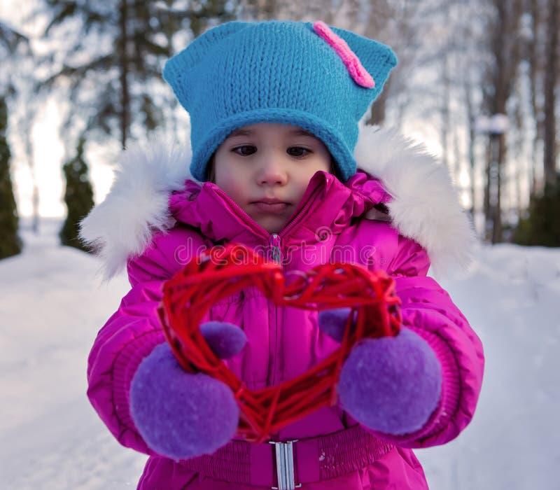 Маленькая девочка держа в их дне ` s валентинки тем сердец рук, дне зимы на улице в парке стоковая фотография rf