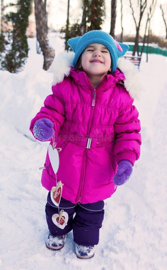 Маленькая девочка держа в их дне ` s валентинки тем сердец рук, дне зимы на улице в парке стоковые фотографии rf