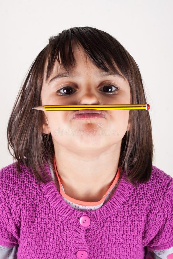 Маленькая девочка держа карандаш любит усик. стоковое фото