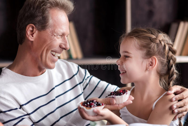 Маленькая девочка держа пирожные с ее дедом стоковое фото