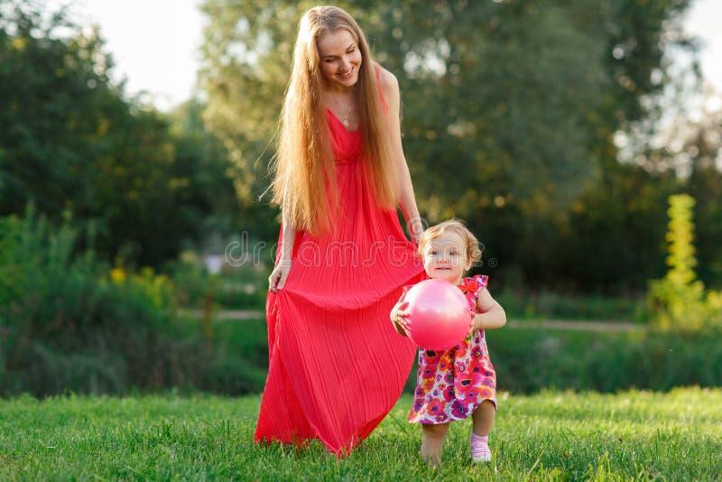 Маленькая девочка держа шарик в руках рядом с матерью стоковые изображения rf