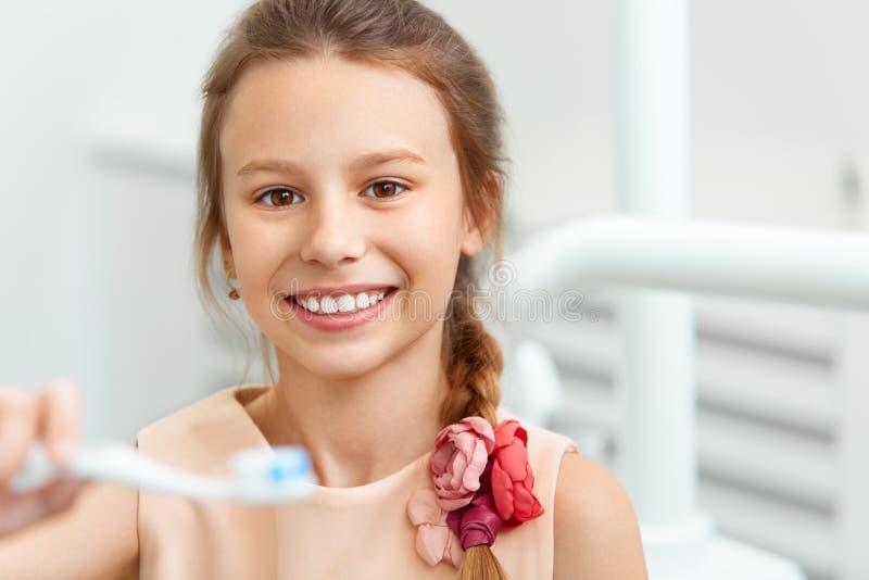 Маленькая девочка держа щетку Teeh чистя щеткой девушка счастливая ее зубы стоковые фотографии rf
