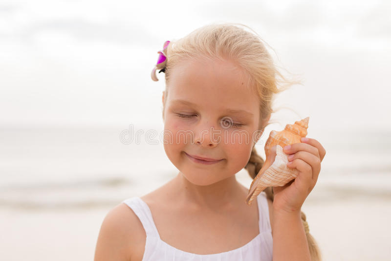 Маленькая девочка держа seashell стоковые изображения rf