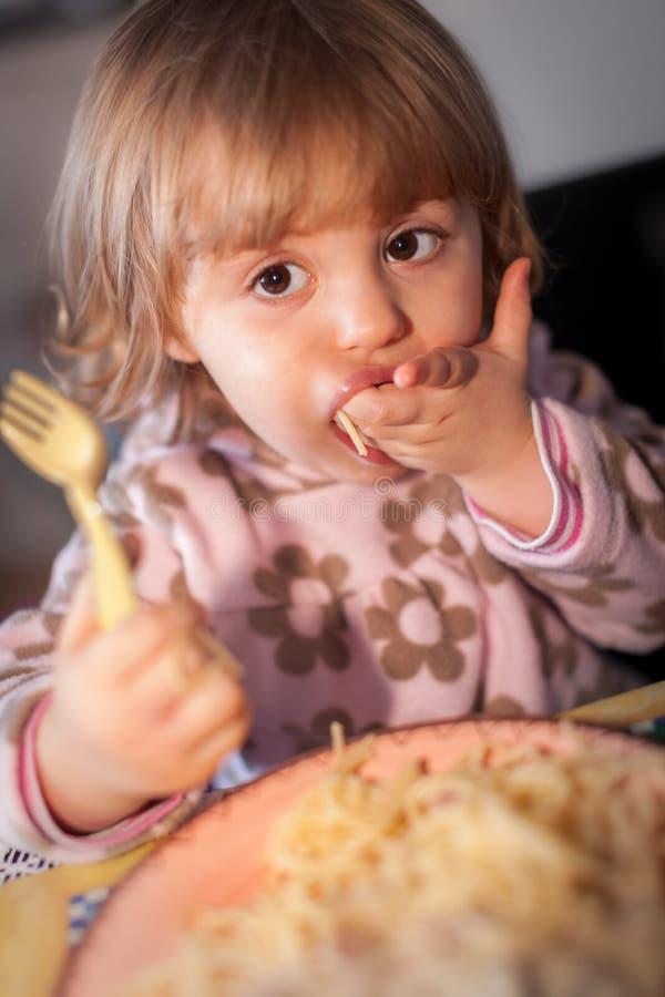 Маленькая девочка есть макаронные изделия стоковые фото