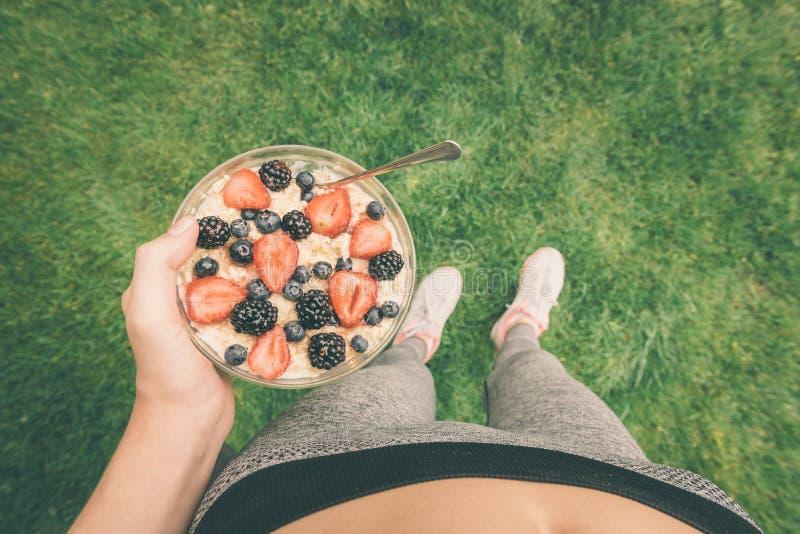 Маленькая девочка есть овсяную кашу с ягодами после разминки стоковые изображения
