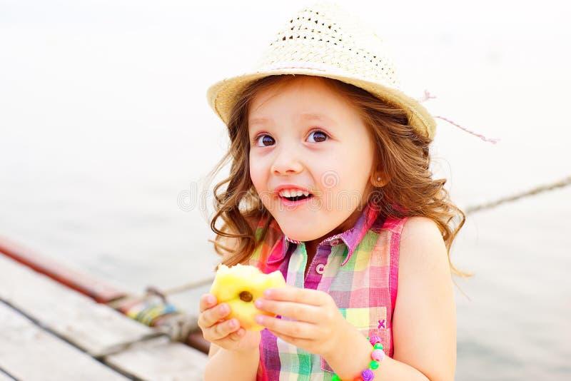 Маленькая девочка есть персик на пристани около озера стоковые изображения rf