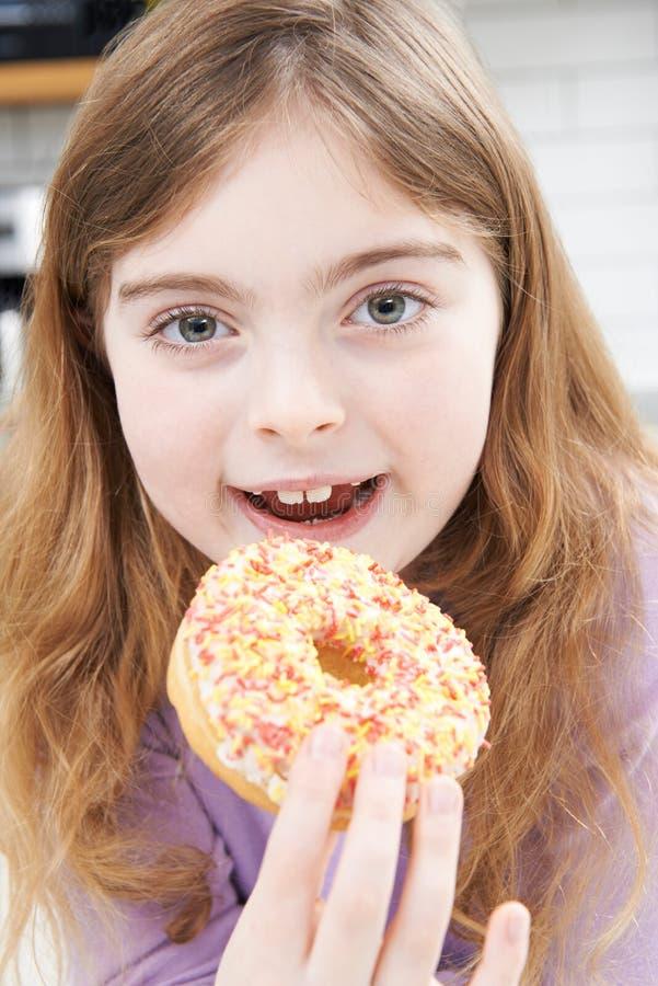 Маленькая девочка есть слащавый донут для закуски стоковые изображения