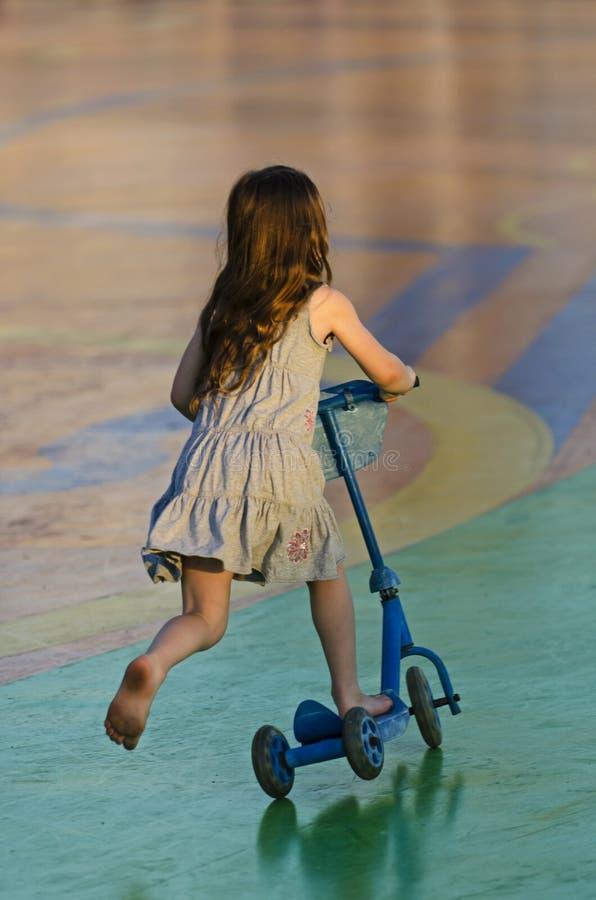 Маленькая девочка ехать самокат outdoors стоковая фотография