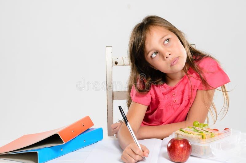 Маленькая девочка делает ее домашнюю работу на таблице стоковое фото rf